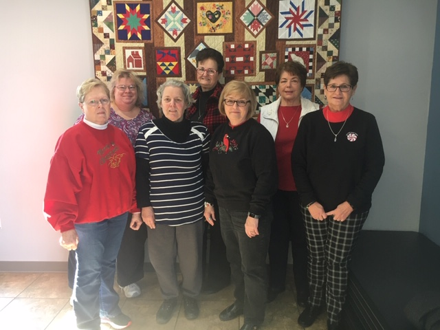 Bicentennial Quilt Display with 7 women standing in front.